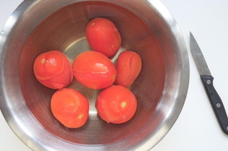 Tomaten ontvellen in bak gekookt water